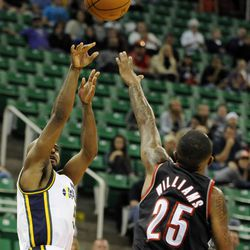 Utah Jazz point guard John Lucas III (5) shoots over the defense of Portland Trail Blazers point guard Mo Williams (25) in the second half of a game at EnergySolutions Arena on Wednesday, October 16, 2013. Lucas III has played all over the globe during his basketball career.