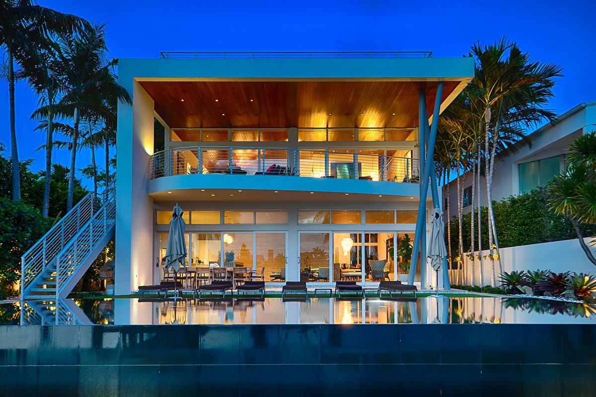 A tropical modern home with an infinity pool out back