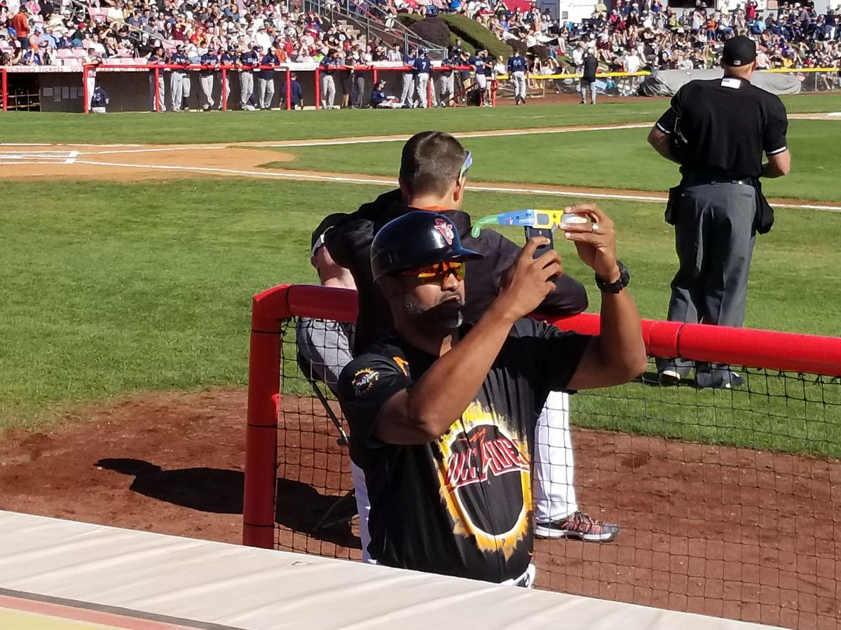 A Volcanoes player takes a cellphone picture of the solar eclipse through special glasses