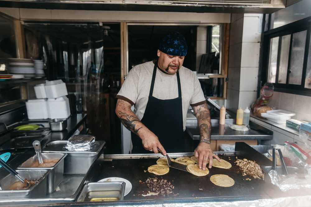 A man in a hat and an apron flips tortillas on a flat top grill inside the window at Taqueria El Rey.