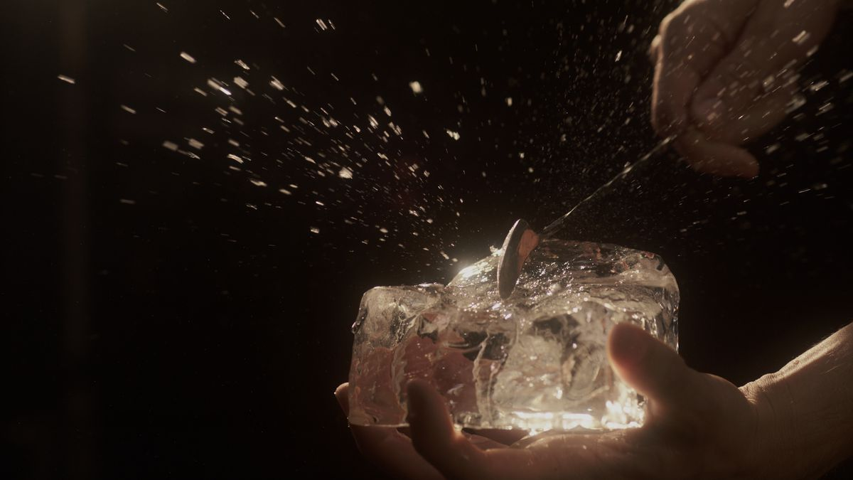 A silver bar spoon hits a chunk of ice, causing ice bits to spray out.