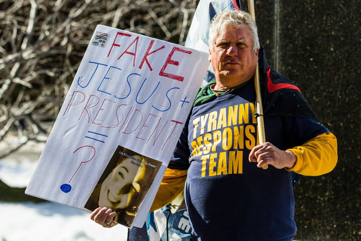 "A person in a ""Tyranny response team"" T-shirt holds a handmade sign that reads ""Fake Jesus plus president equals ?"""