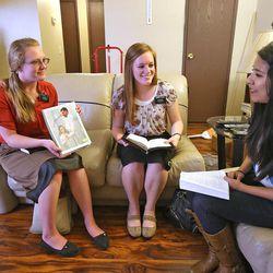 Sister Skyla Hill, left, from North Carolina and Sister Emily Veazey, from North Dakota, talk to investigator Karina Alvarez in her home, Friday, March 14, 2014, in Henderson.