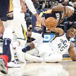 Utah Jazz guard Donovan Mitchell (45) dives to the ground to fight for a loose ball with New Orleans Pelicans guard Rajon Rondo (9) as Utah hosts New Orleans at Vivint Arena in Salt Lake on Friday, Dec. 1, 2017.
