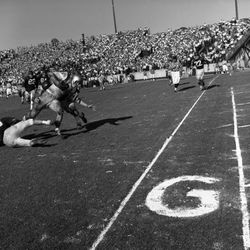 1963-#21 FB Larry Brinkley being tackled during FSU football game in Tallahassee against Virginia Tech University.