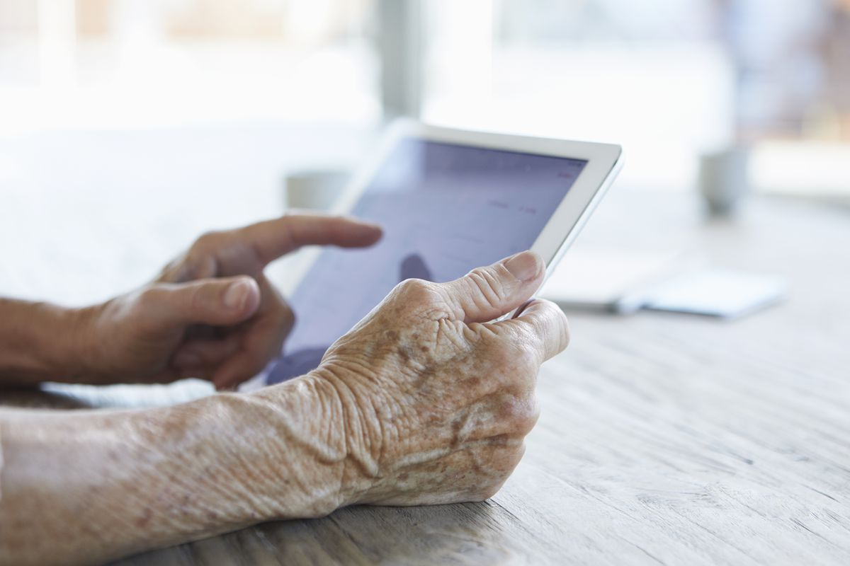 Hands holding and pointing to a touchpad resting on a table.