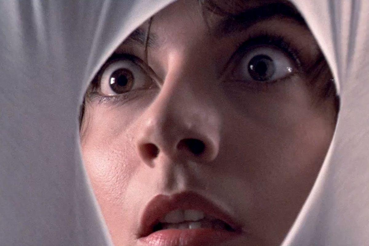Tenebrae (1982): A woman looks through a white cloth