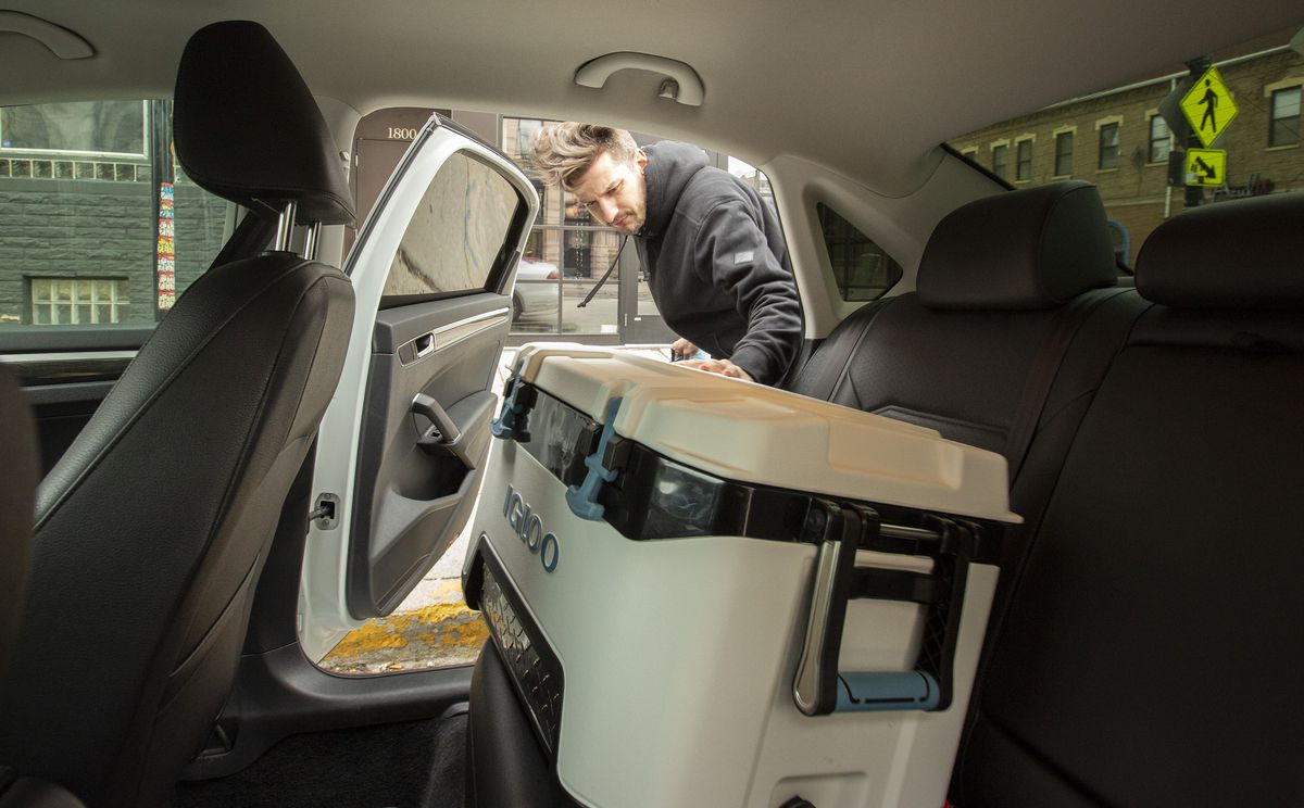 A map puts a large cooler into the back seat of a car.