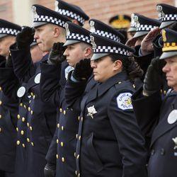 Officers salute as pallbearers place Officer Jimenez's casket into the hearse. | Ashlee Rezin/Sun-Times