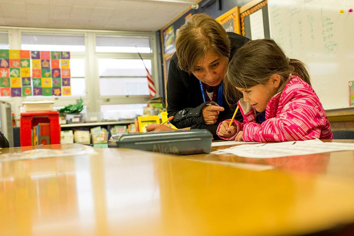 Paraprofessional Bertha Finney works with a first-grade student on a writing assignment at Denver's Goldrick Elementary School in 2017.
