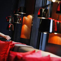 This  Friday, March, 16, 2012 photo shows maid adjusting cushions in a room of one of the luxury penthouse apartments overlooking Hyde Park, London which is available for hire during the London 2012 Olympics for some 11,000 British pounds (US$17,600) a night - and includes a maid a butler and and Aston Martin car.