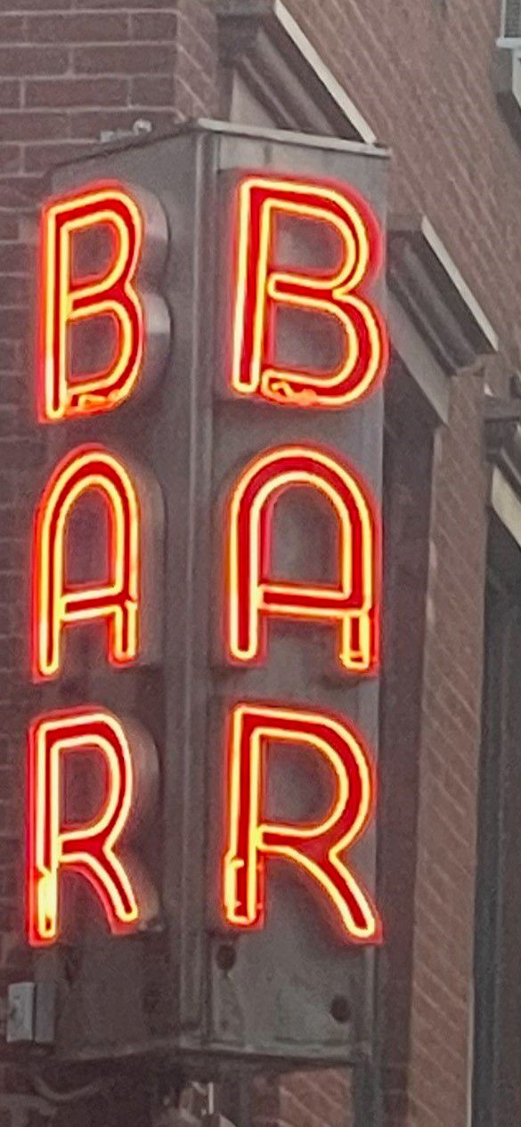 """A neon sign that spells out """"Bar"""" in Italy."""
