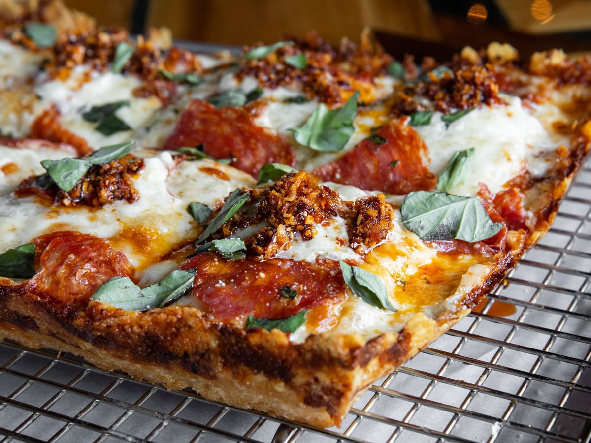 a rectangluar Detroit-style pie with an ultra-cheesy crust