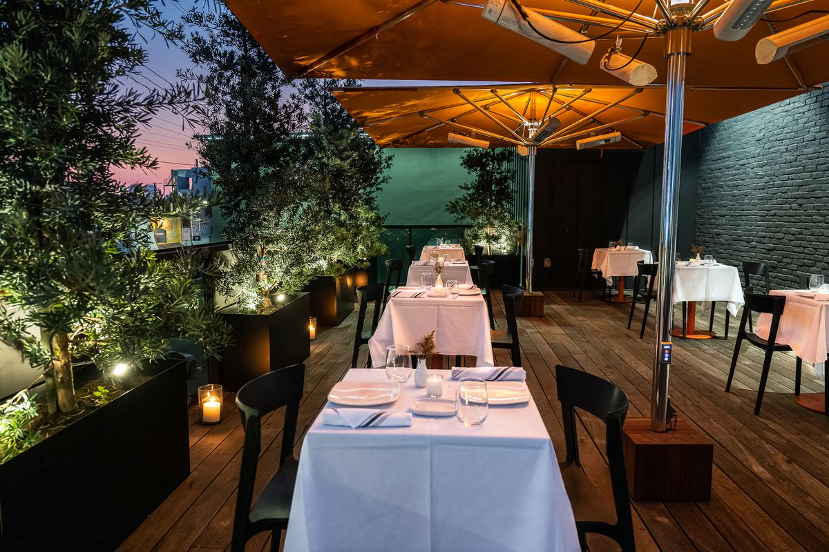 An evening rooftop patio with white tablecloths.