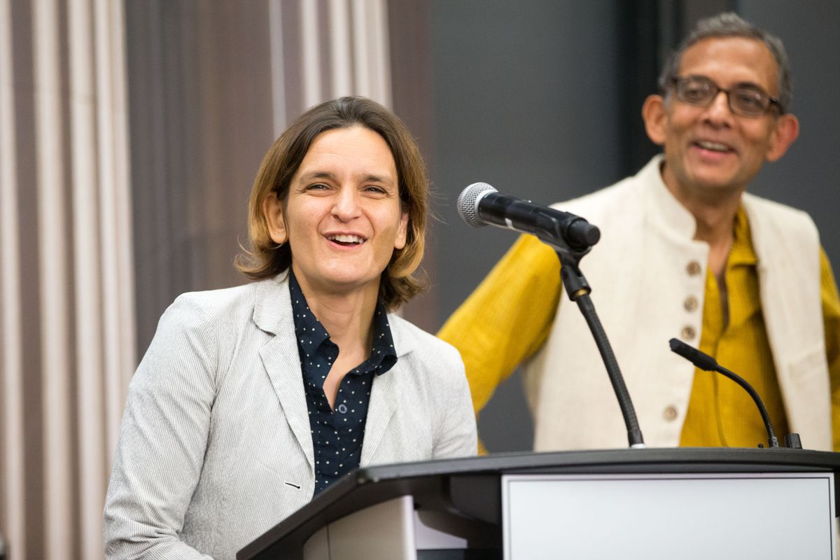 MIT's Esther Duflo and Abhijit Banerjee stand at podiums to take press questions after winning the 2019 Nobel Prize for economics.