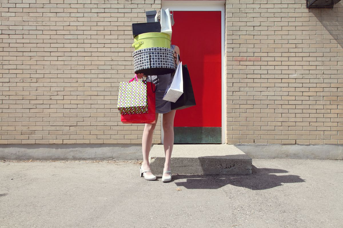 A woman in high heels and a dress juggling shopping bags and boxes stacked high above her head.