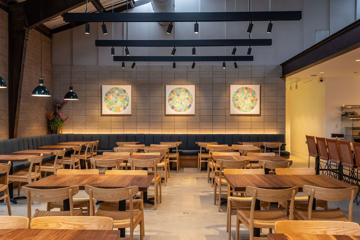 A collection of wooden tables inside of a large warehouse-y restaurant, with the open kitchen at the right.