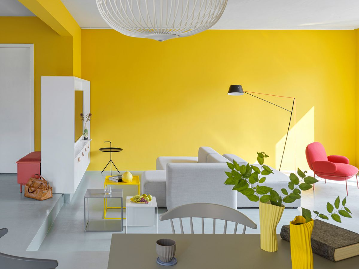 Living room with yellow walls, gray sofa, and a pink armchair.