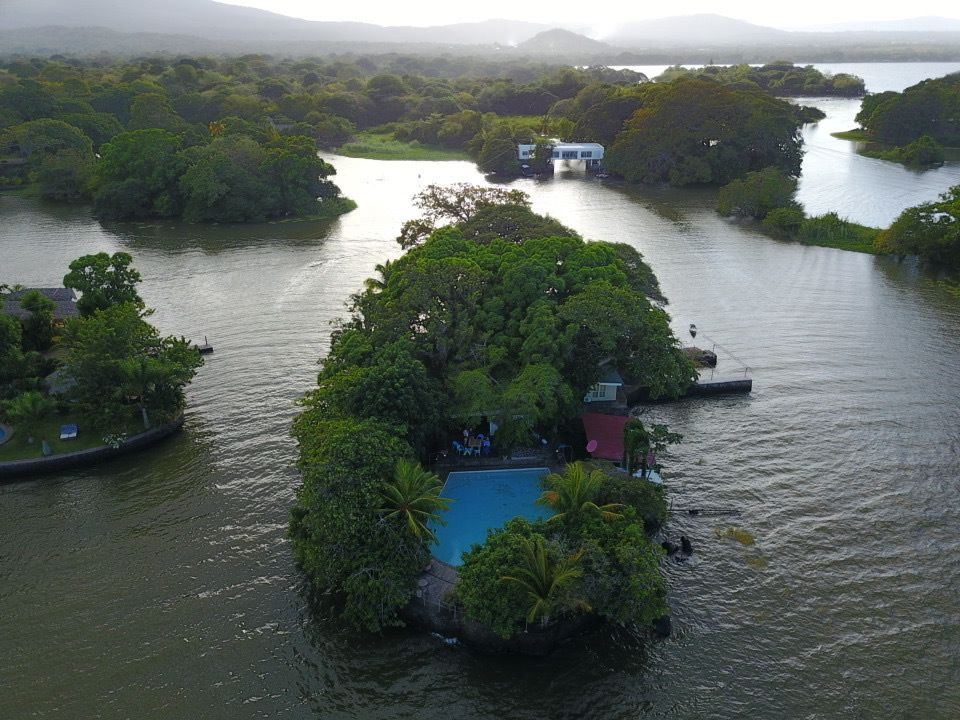 An aerial view of a lush green island. You can see the pool and the island is surrounded by water with mountains in the background.