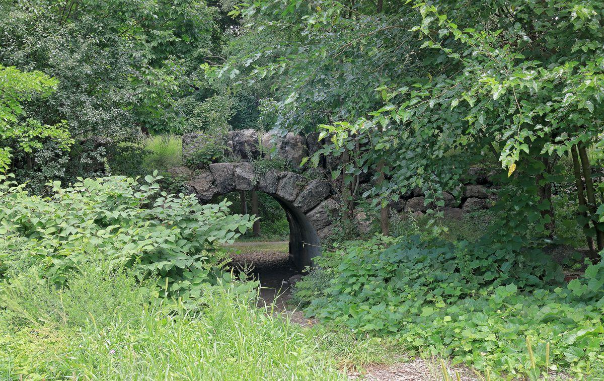 A lush park with a puddingstone bridge tucked amid the foliage.
