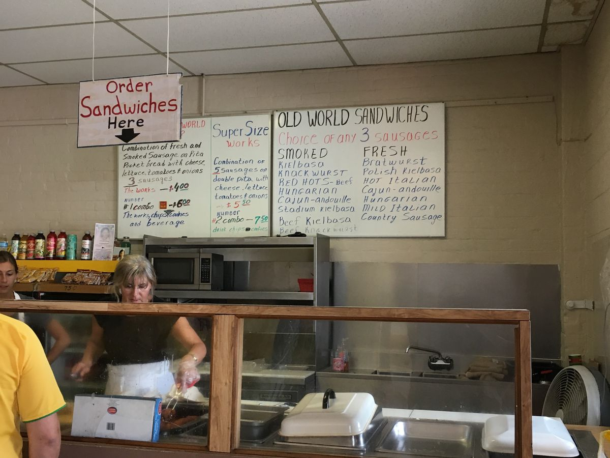 """A woman stands under the """"Order Sandwiches Here"""" sign at Eastern Market Seafood."""