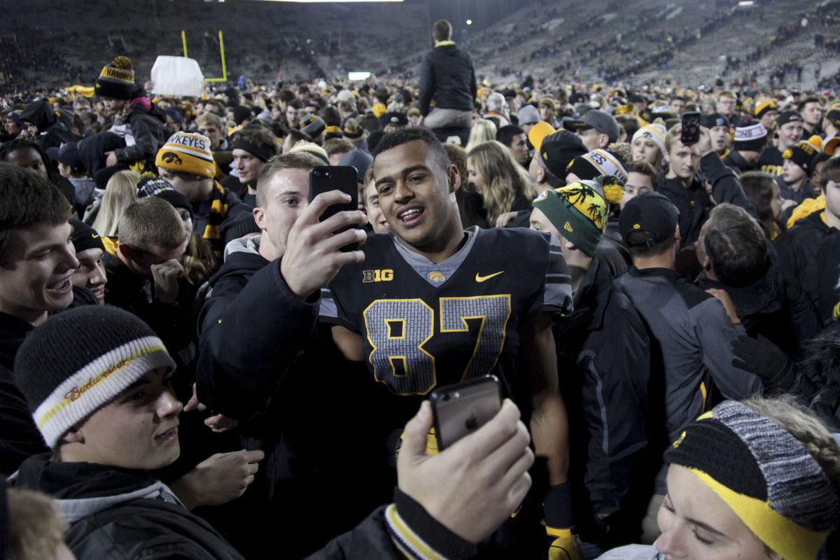 IOWA CITY, IOWA- NOVEMBER 04:  Tight end Noah Fant #87 of the Iowa  Hawkeyes poses with fans on the field after the upset of the Ohio State  Buckeyes on November 04, 2017 at Kinnick Stadium.