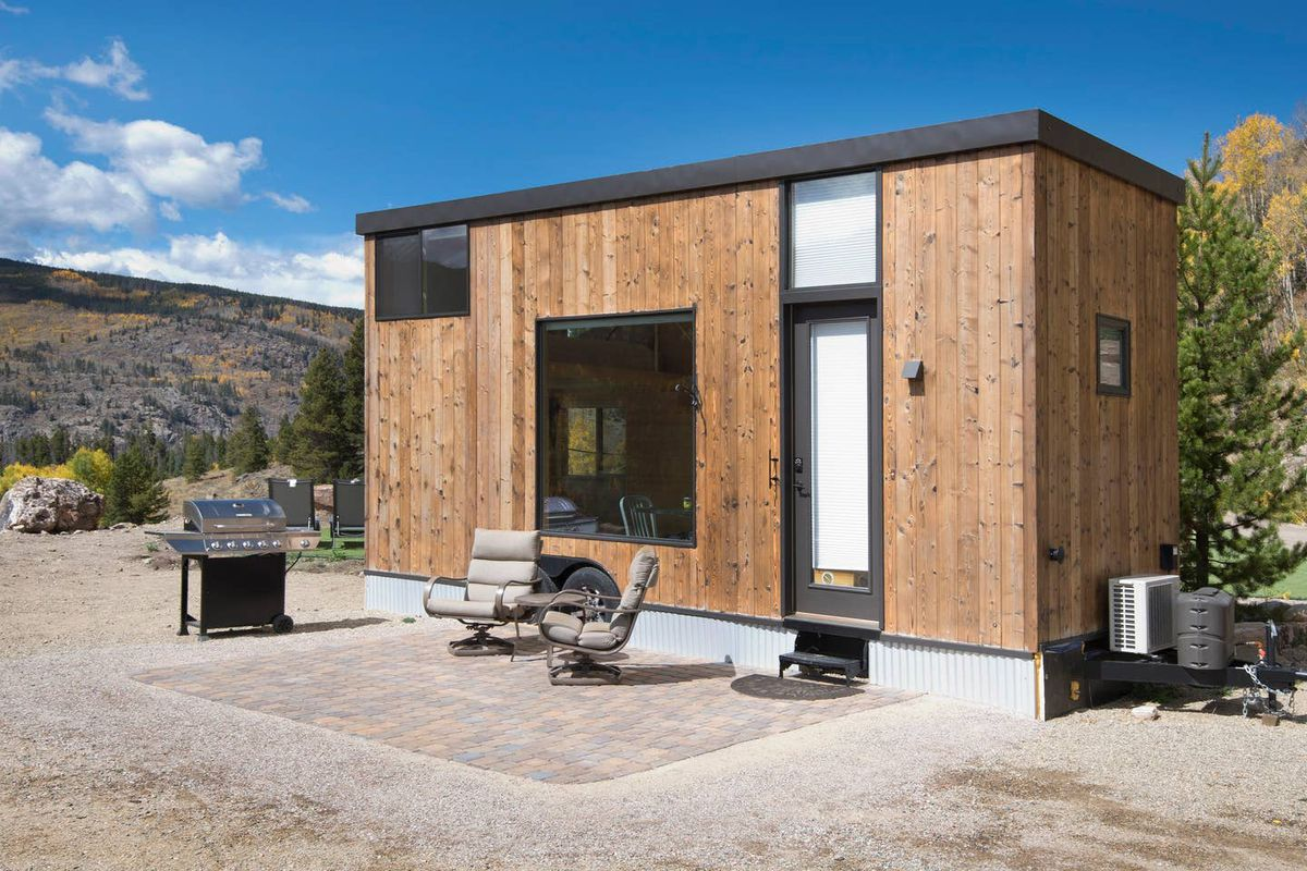 A boxy wooden tiny home features black windows and two chairs in front of it.