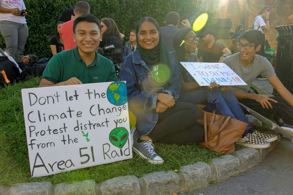 """Protesters at the Global Climate Strike in New York City sit on a grassy bank and hold signs. The signs read, """"Don't let the climate change protest distract you fro the Area 51 raid,"""" and, """"I want to see my twenties!!!"""""""