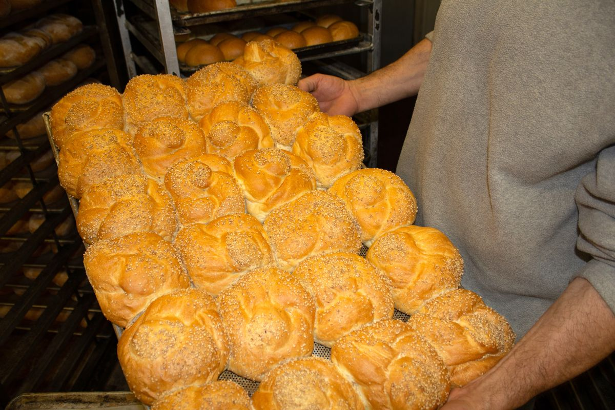 A man with a grey shirt holds a sheet pan full of sesame seed buns inside the production space of a bakery
