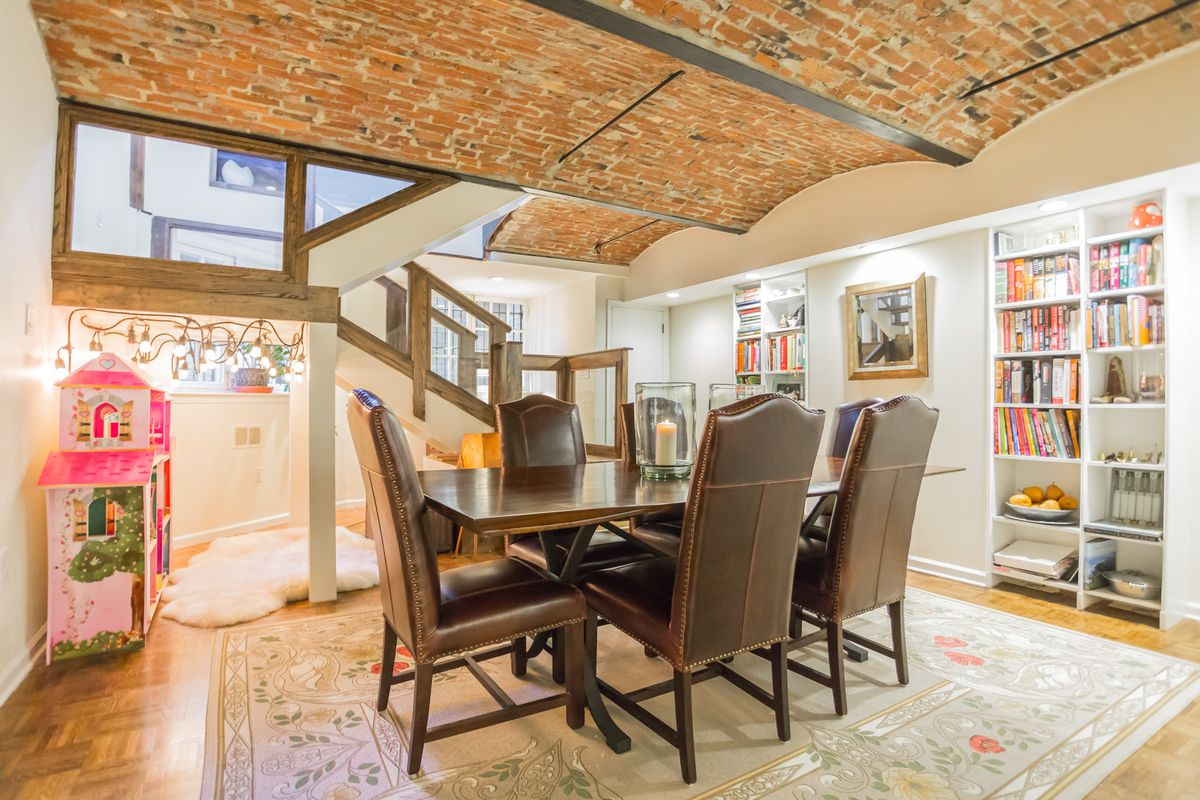 A lower-level dining room with brick barrel ceilings and a wall of white built-ins.
