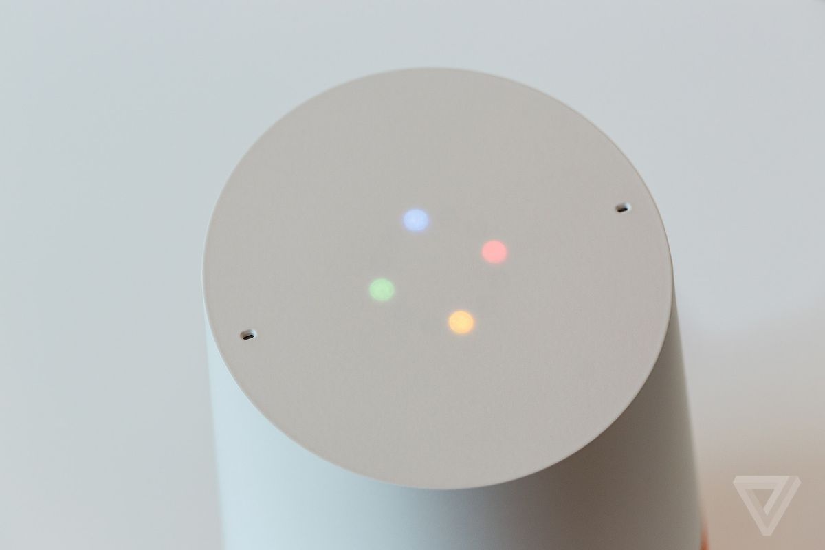 The top of the Google Home speaker, which is white with four lights in a diamond pattern: blue, red, yellow, green