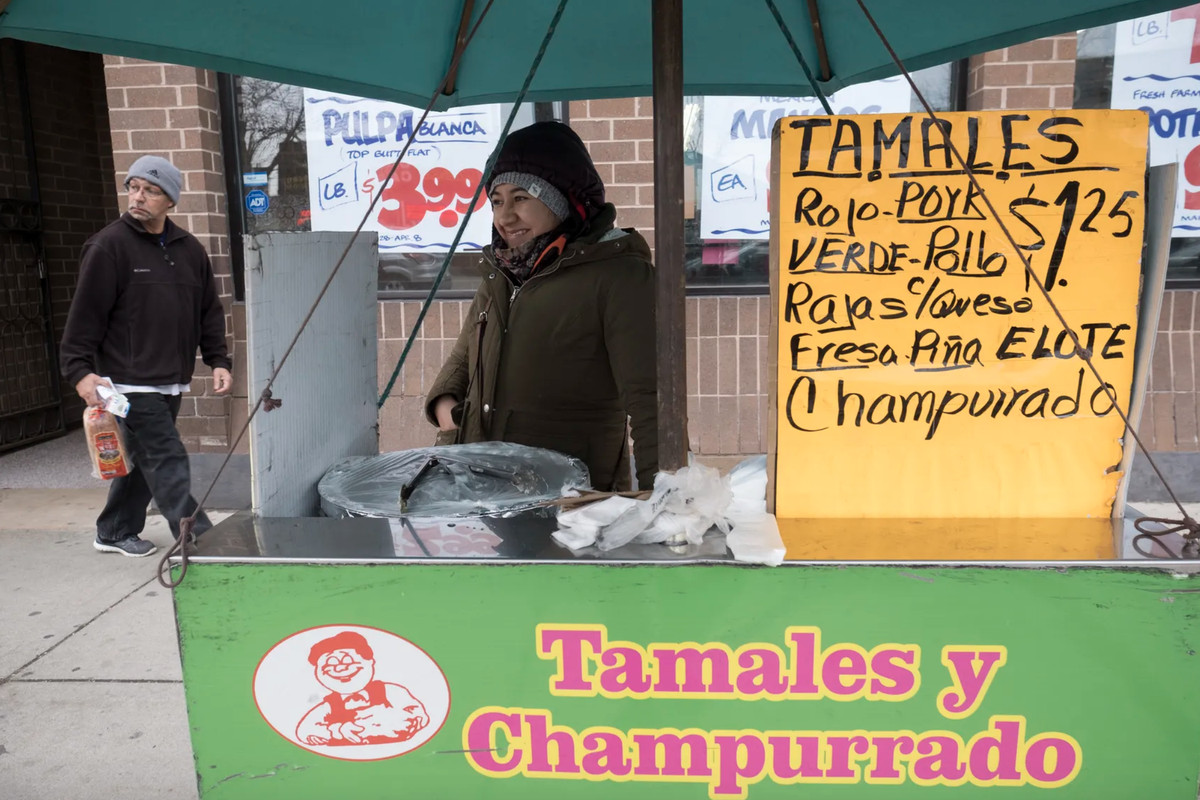 """A smiling woman behind a green cart that reads """"Tamales y Champurrado"""""""