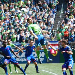 Zach Scott catches air to get his head on the ball above Colorado's defenders.