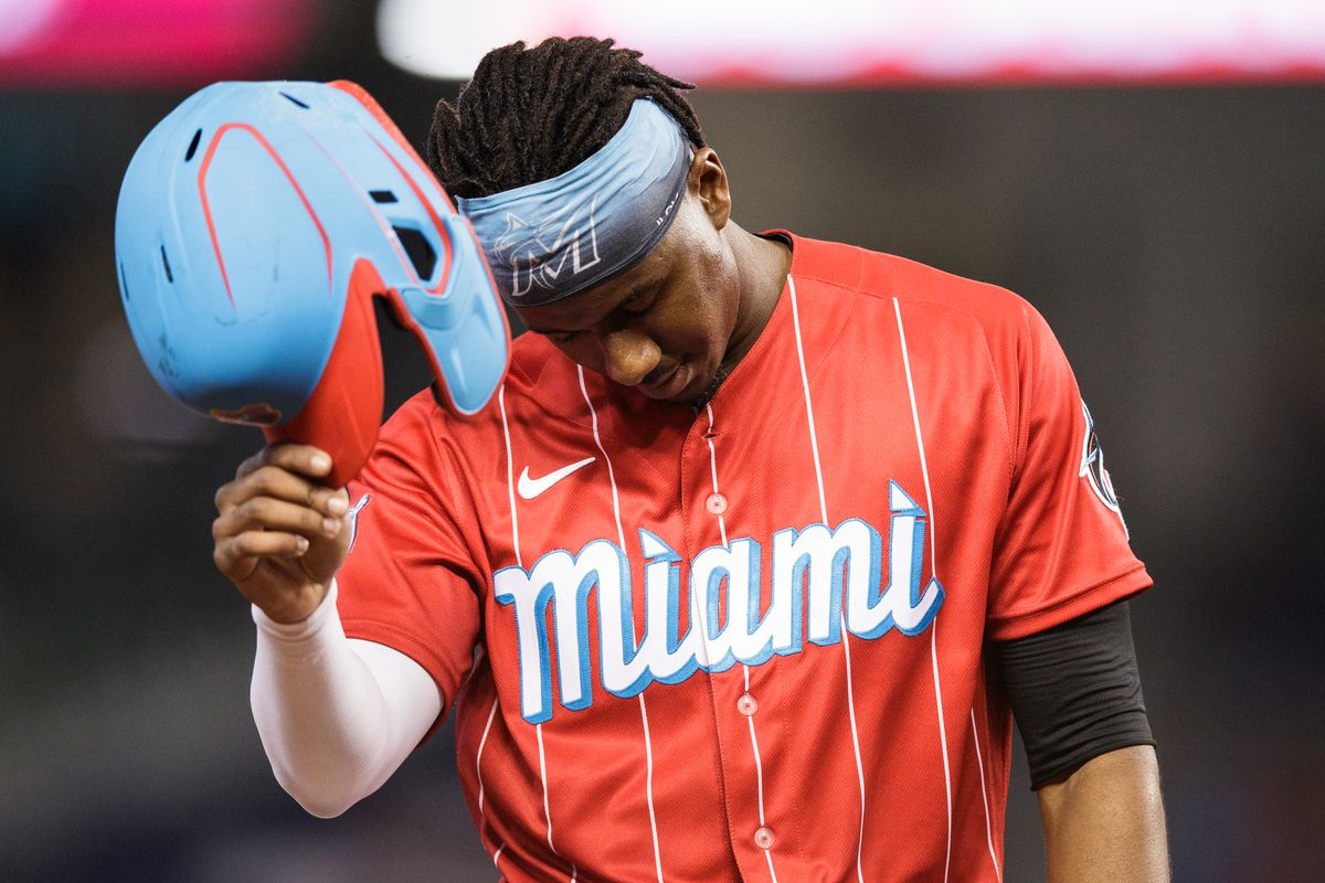 Lewis Brinson #25 of the Miami Marlins takes off his helmet after being tagged out on a rundown play at third base in the sixth inning against the Philadelphia Phillies at loanDepot park