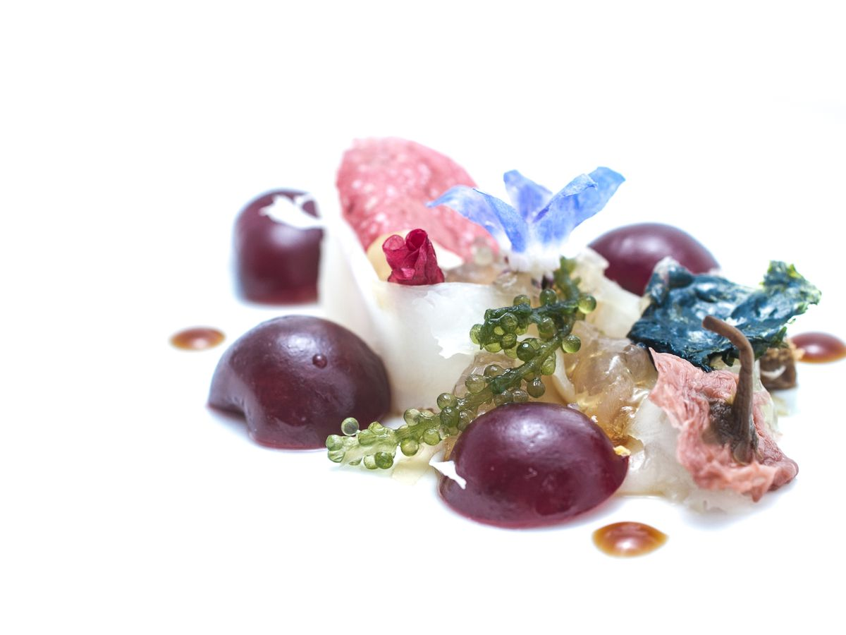 A playfully plated dish with grapes and flowers.