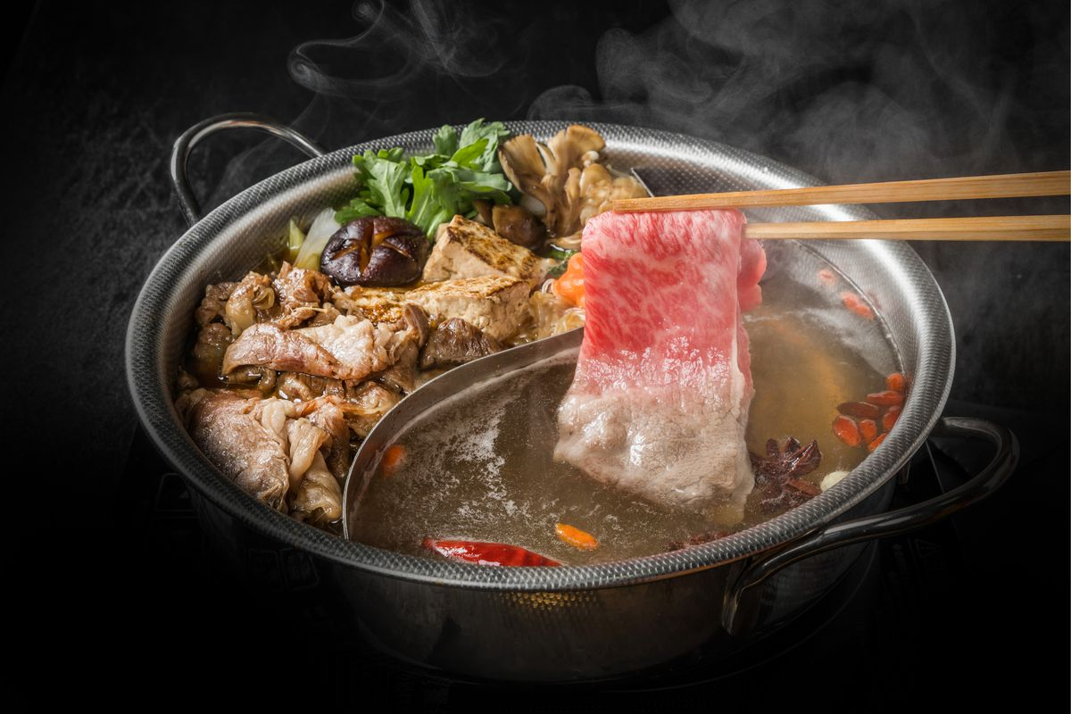 A pair of chopsticks holding a piece of meat over a bowl of Chinese hot pot soup