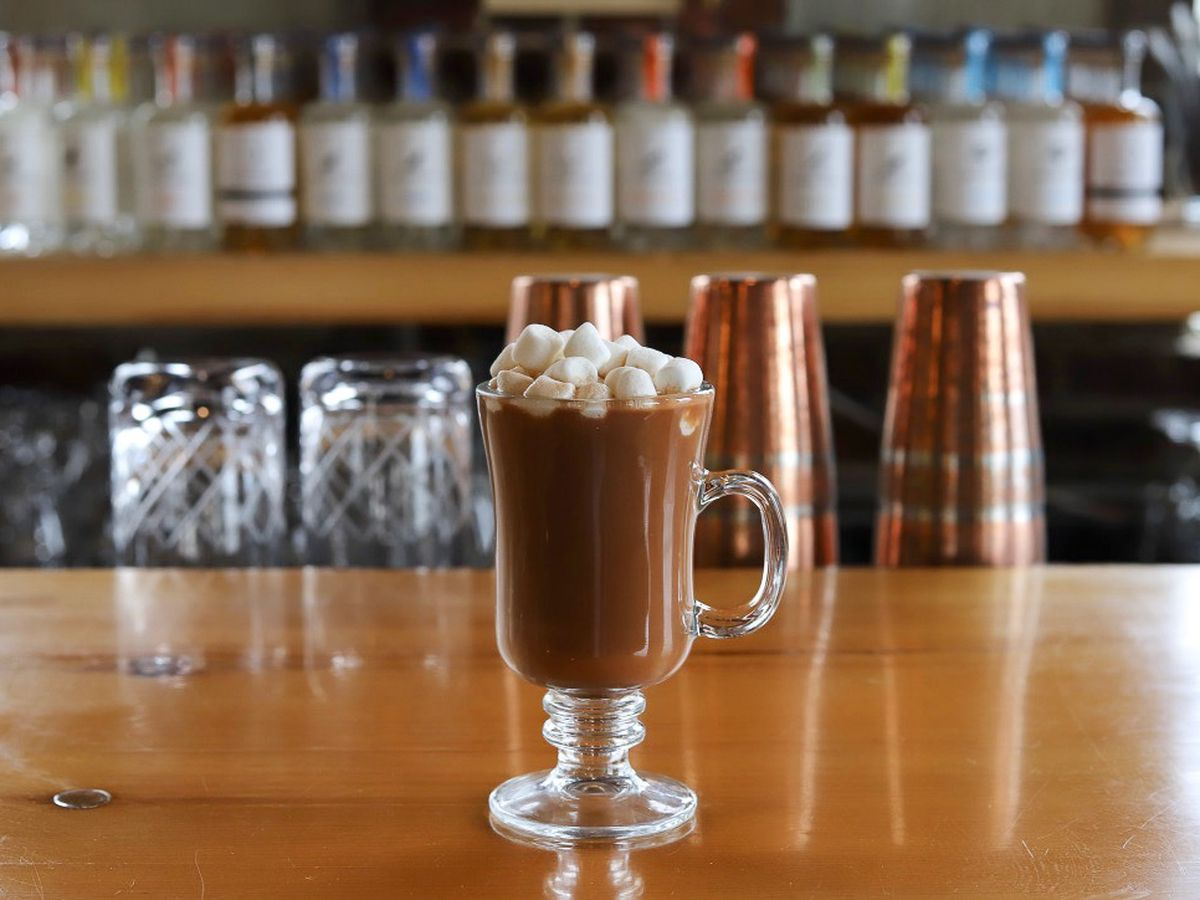 A boozy hot chocolate in a clear glass mug sits on a bar and is garnished with ample marshmallows