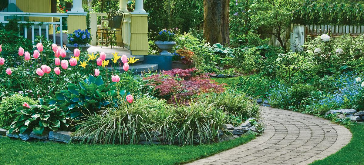 Walkway surrounded by plants and flowers leading up to a patio.