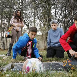 Jenni Thompson and her three boys Davin, Cade and Creed visit the grave of her husband, Bryce, at the Murray Cemetery in Murray Nov 19, 2014. Several Thompson family members have died from cancer.