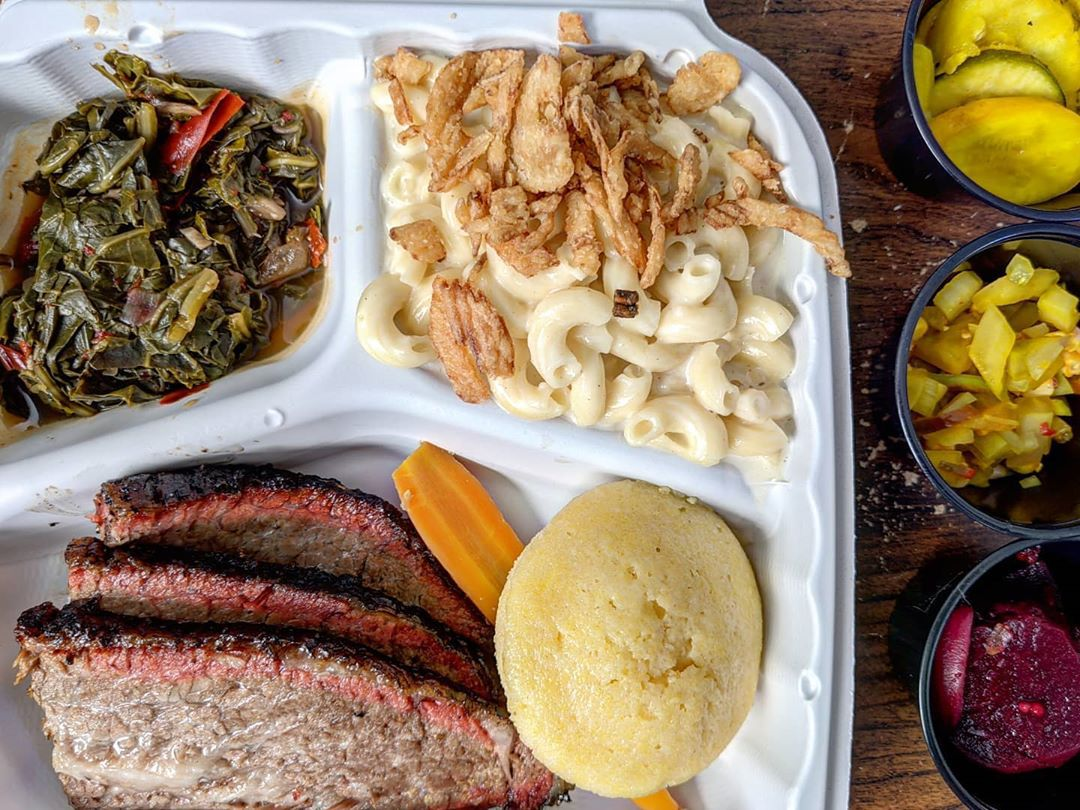 Overhead view of a white paper takeout container of brisket, mac and cheese, collared greens, and cornbread. Three small black takeout cups of pickles are lined up next to the container.