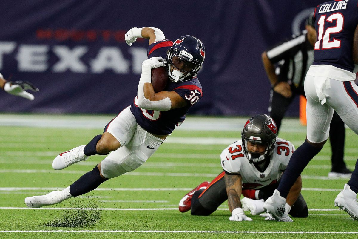 Phillip Lindsay #30 of the Houston Texans is tripped up by Antoine Winfield Jr. #31 of the Tampa Bay Buccaneers in the first quarter during a NFL preseason game at NRG Stadium on August 28, 2021 in Houston, Texas.