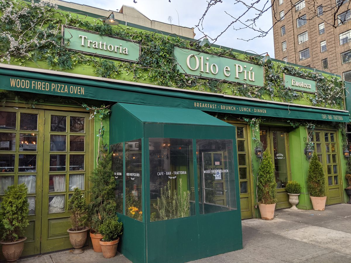 The front facade of a restaurant that is green, covered in ivy, and has a box out front for providing warmth from the cold.