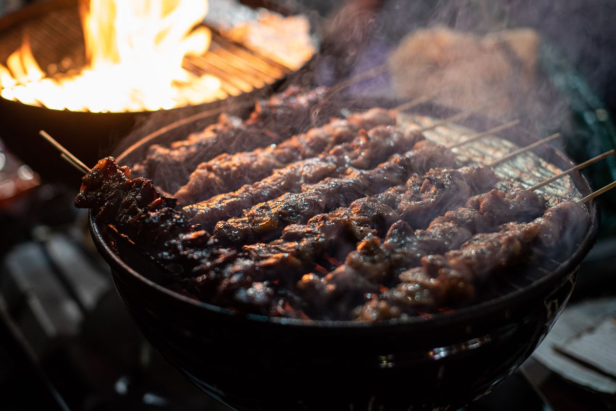 An up close look at crowded meat skewers on a charcoal grill.