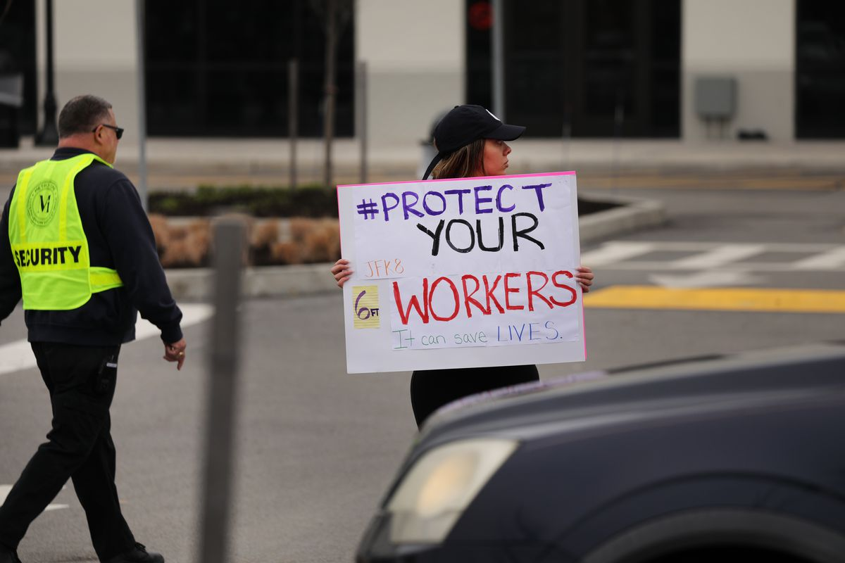 """A protester holds a sign that reads, """"Protect your workers."""""""