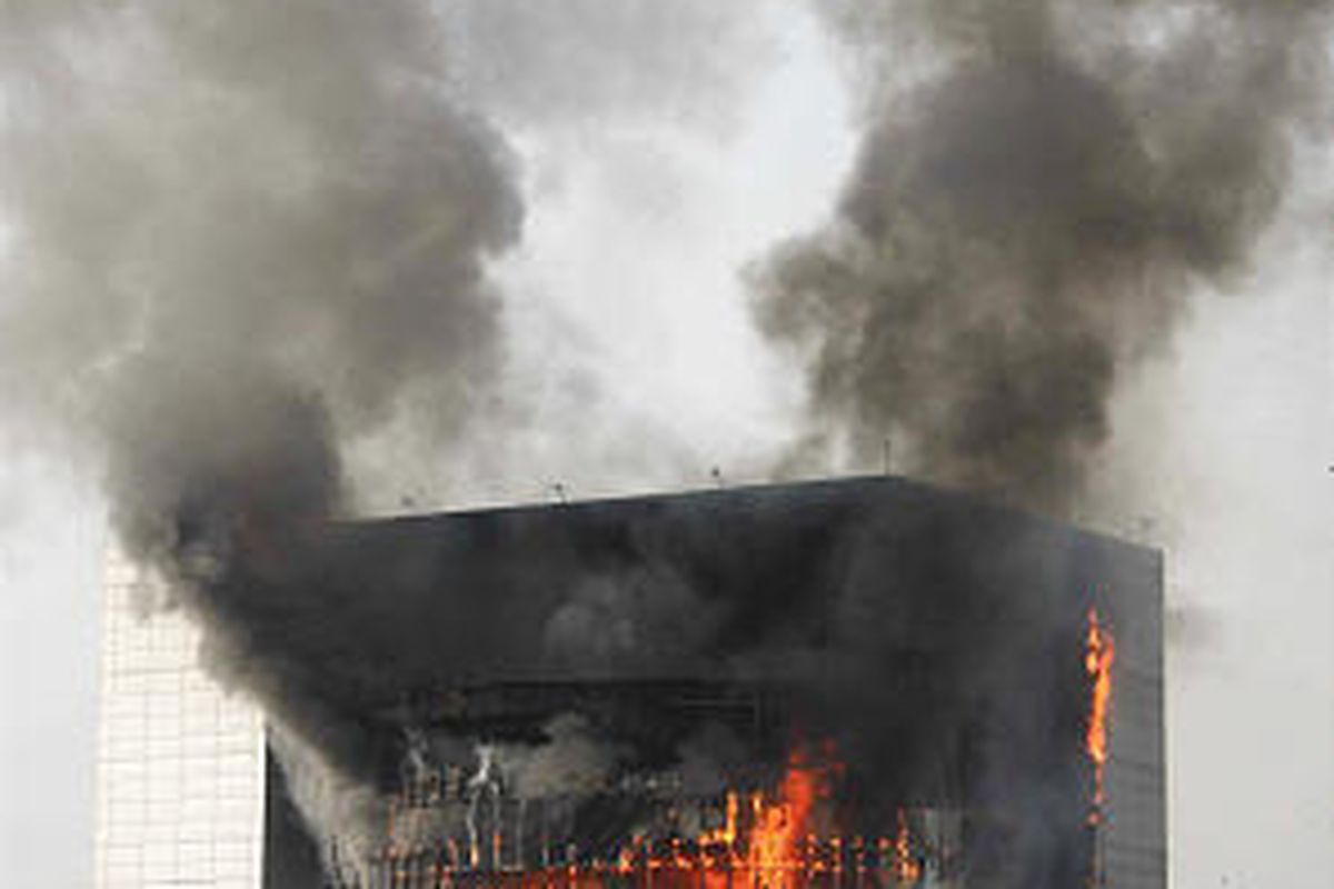 A rescue helicopter flies over the burning 22-story Bashundhara City shopping mall on Friday.