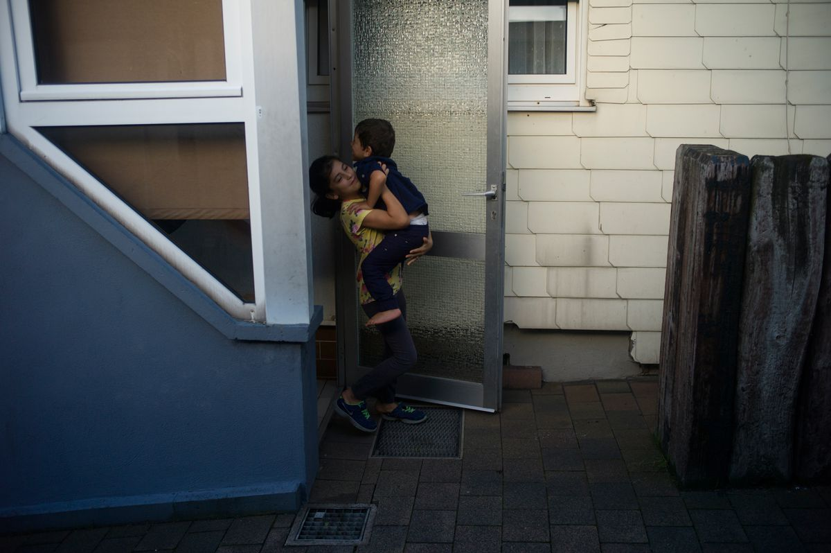 Syrian refugee Nour Al Hammoud, 10, carries her little brother Wessam, 3, out of the front door of their family's home in Neu-Anspach, Germany, on Friday, Sept. 13, 2019. The family has resettled multiple times since coming to Germany, first landing in an emergency refugee shelter, later in a shared apartment complex, and now in their own home.