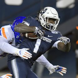 Utah State running back Gerold Bright (1) gets tackled by Boise State linebacker Demitri Washington during the second half of an NCAA college football game Saturday, Nov. 23, 2019, in Logan, Utah.