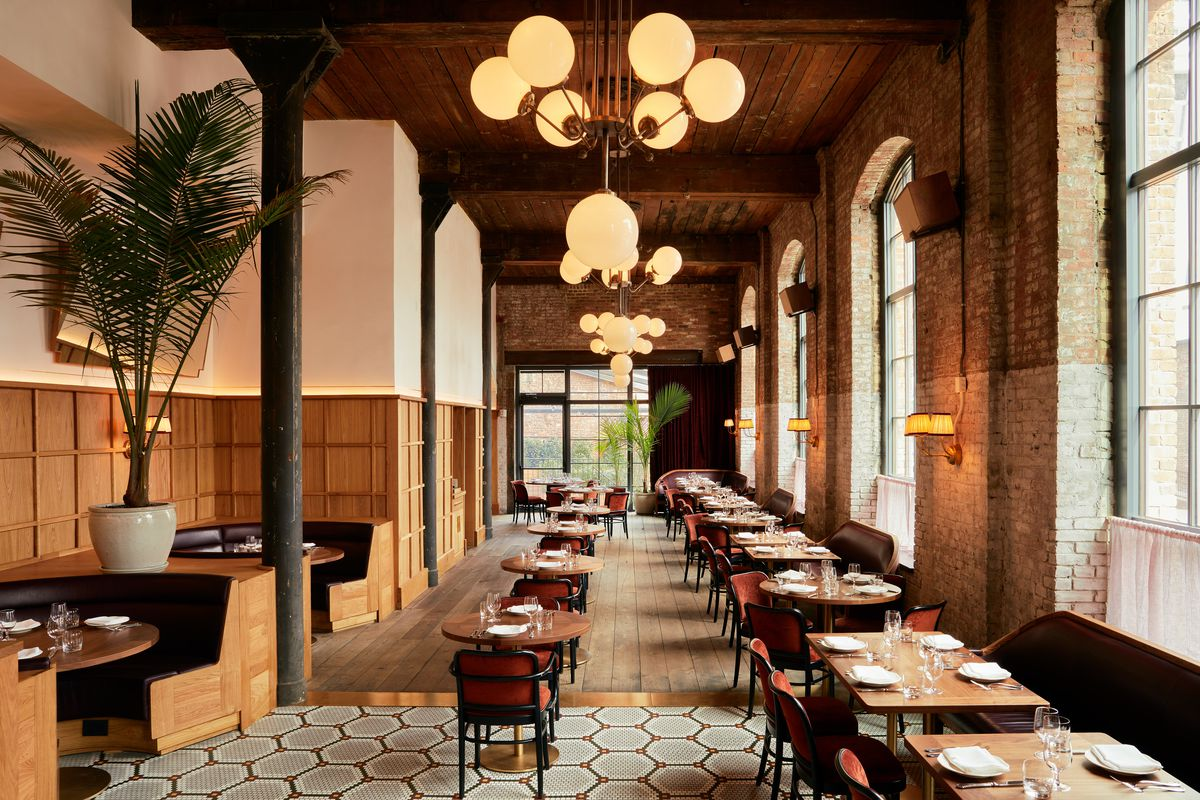 The interior of a restaurant with a giant palm tree, a row of wooden tables and chairs, and large arched windows