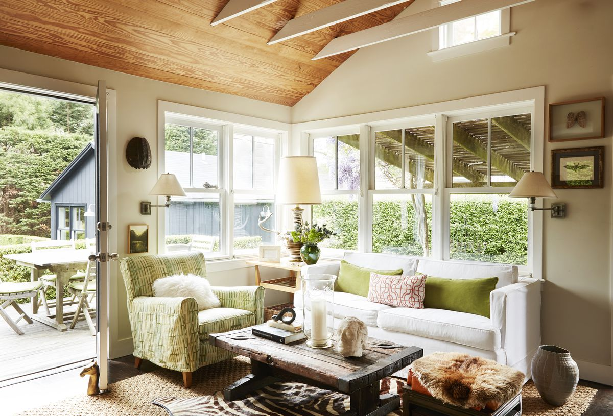 The living room has white walls and wood ceilings.