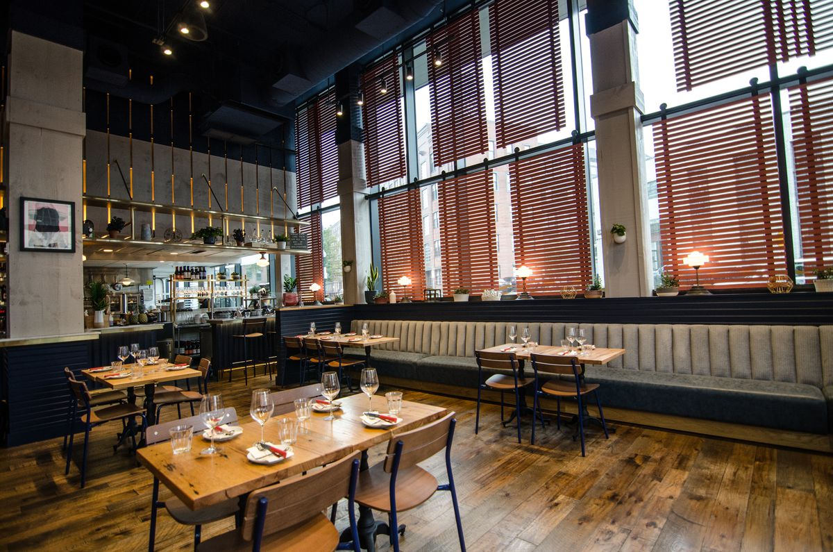 A high-ceilinged restaurant interior features a wooden floor, wooden tables and chairs, off-white banquettes and accents, navy blue accents, and rose slats over the windows. An open kitchen is visible in the background.